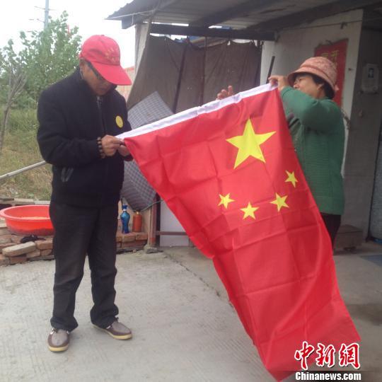 临近国庆,赵伦波老人换了一面新国旗,正在与老伴整理国旗。 刘林 摄