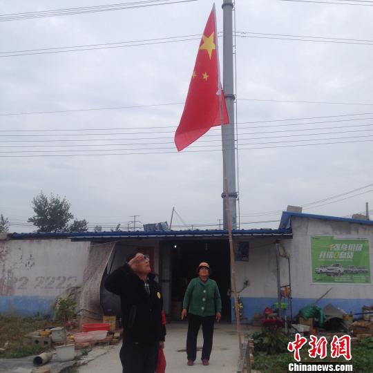 国旗升起后,赵伦波向国旗敬礼。 刘林 摄