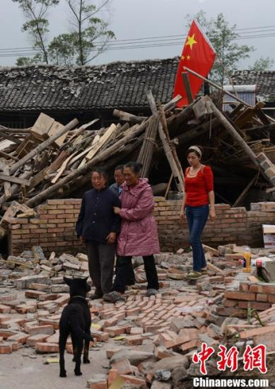 资料图。一位雅安当地民众在家人的搀扶下离开自家废墟,他们在地震中失去亲人。中新社发 张元 摄