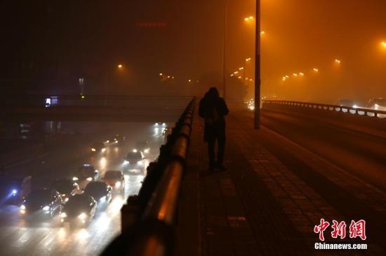 11月5日早晨,北京大雾弥漫,部分地区出现能见度不足200米的强浓雾。同时中到重度霾持续。北京市气象台11月4日晚21时发布大雾橙色预警信号,预计至11月5日早晨本市大部分地区有能见度小于200米的浓雾,局地能见度小于50米。图为11月4日晚上,北京被雾霾笼罩。中新社记者 富田 摄