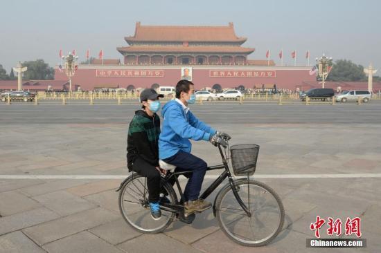11月3日,北京大气扩散条件转差,空气污染指数持续攀升。据悉,北京已于2日傍晚发布空气重污染黄色预警。图为一对青年佩戴口罩骑车经过北京天安门广场。 中新社记者 崔楠 摄
