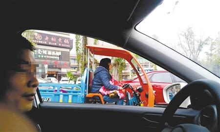 女子抱着孩子骑三轮车沙区警方供图