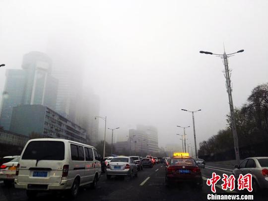 乌鲁木齐河滩快速路雾气严重,道路有薄冰,车辆缓慢行驶。 赵晓咏 摄