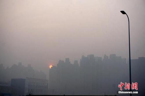 资料图:2016年1月3日,河南郑州雾霾笼罩着的高楼大厦。中新社记者 王中举 摄