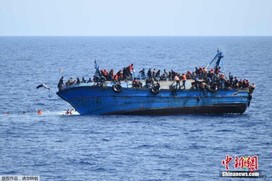 资料图片:利比亚近海海域,一艘满载难民的船只即将倾覆,船上的难民纷纷跳海逃生。