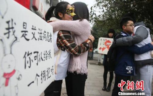 """资料图:大学生扮""""艾滋病患者""""求拥抱,宣传防艾知识。曹正平摄"""