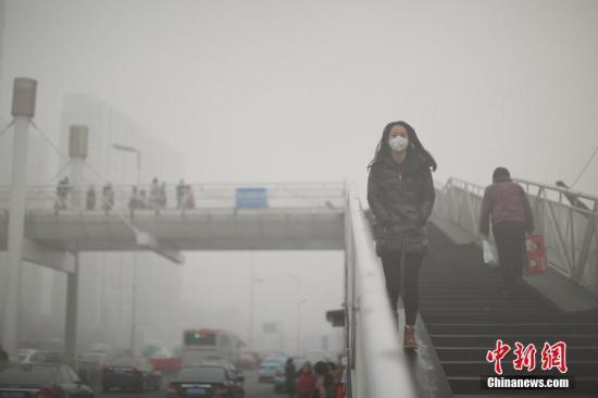 资料图 戴着口罩的行人从天桥上走过。中新社记者 佟郁 摄