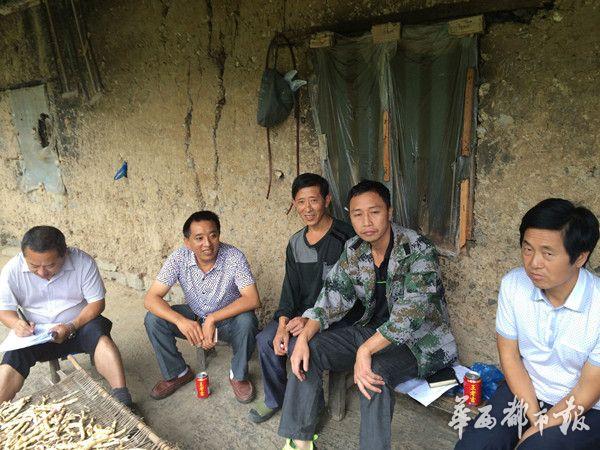 罗林章搜集扶贫户资讯(左一)。
