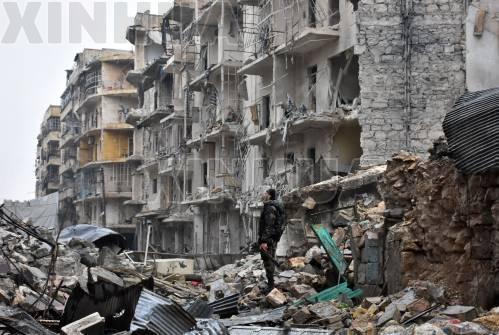 12月13日,在叙利亚阿勒颇,一名叙政府军人员站在遭到严重破坏的街道上。(新华社/法新)
