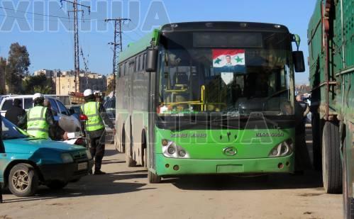 12月15日,在叙利亚阿勒颇,用于反政府武装人员及其家属撤离的巴士停靠在路边。 (新华社/法新)