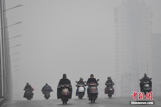 资料图:12月13日,山西太原,民众在雾霾中出行。