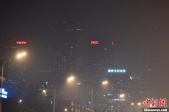 12月15日,北京发布今年首个空气重污染红色预警。图为12月16日晚间,北京的高楼大厦在雾霾中若隐若现。中新网记者 金硕 摄