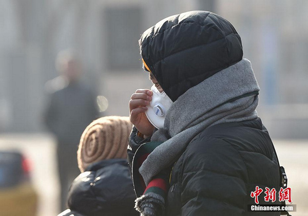 """昨天,北京霾持续,市民戴口罩""""全副武装""""出行。图片来源:中新网"""