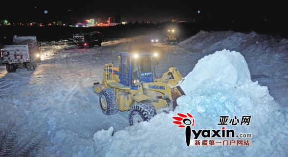 12月25日0:35,乌市水磨沟区帕米尔街雪场,推土机正在将雪推到一起。亚心网记者谢鹏摄