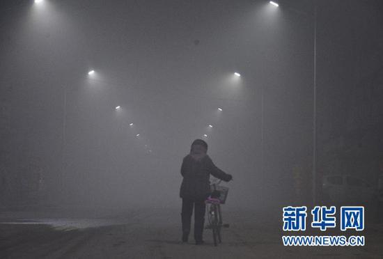 1月3日晚,一名行人推车走在大雾笼罩下的山东省聊城市茌平县贾寨镇街头。中央气象台1月3日18时继续发布大雾红色预警:预计,3日20时至4日20 时,北京南部、天津、河北中南部、河南中东部、山东、安徽、江苏、浙江北部、山西南部、陕西关中等地有大雾,其中部分地区有能见度低于50米的特强浓雾。 新华社发