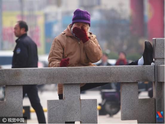 ▲1月10日,山西省临汾市陌头一名大妈一边压腿训练一边用手捂住鼻子(图像来历:视觉国家)