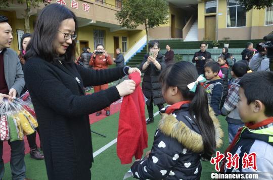 """资料图:重庆妇联工作人员为留守儿童发放""""爱心毛衣""""。 钟欣 摄"""