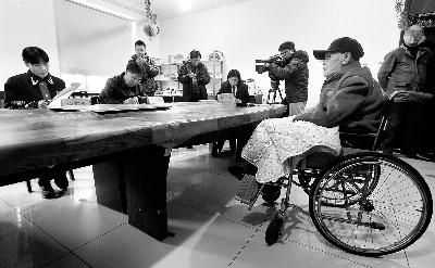 被告人孙某坐在轮椅上接受法官庭审