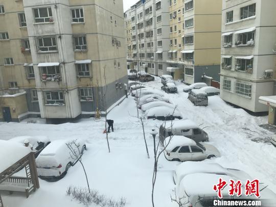 暴雪后民众在小区内清理积雪。 迪娜 摄