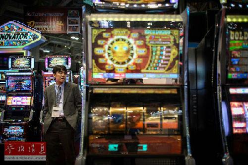 资料图片:一位游客站在澳门的一家赌场内。