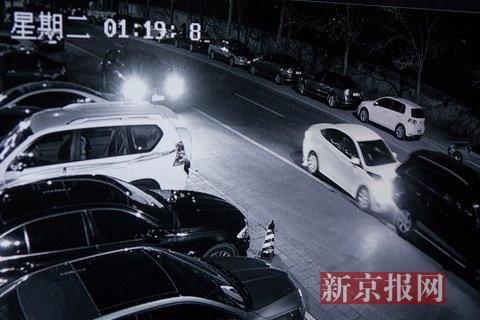 奥迪车突然猛向后退,撞击白色车辆前部,随后从左侧及前方两车夹缝中开出,并撞到站立在左前方的男子,向南逃跑。视频翻拍。新京报记者 李强 摄