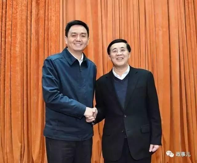 16日上午,李红军(左)和许光(右)在全市领导干部会议上握手