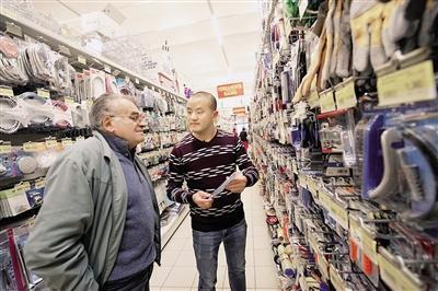 任永洪(右)正在给顾客介绍商品。重庆晨报 记者 吴国富 摄