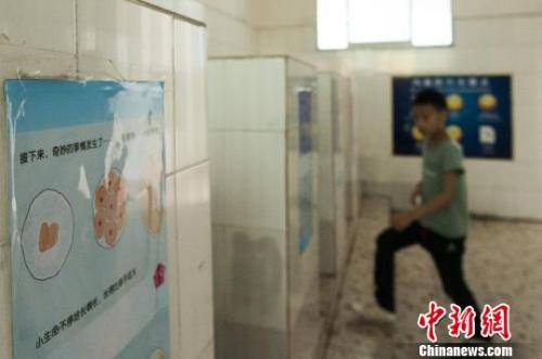 图为广西柳州文惠小学在男厕所悬挂的性知识绘本,让学生在排队上厕所,或蹲厕所时,抬头即能看见。 黄威铭 摄