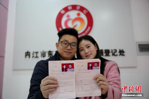资料图:2016年2月14日,在四川省内江市东兴区婚姻登记处,一对新人在展示刚领取的结婚证书。兰自涛 摄