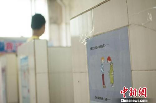 图为广西柳州文惠小学在男厕所悬挂的性知识绘本,图文并茂的讲述,给学生进行性教育。 黄威铭 摄