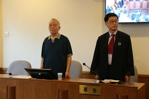 一审时,季承(左)在法庭上。北京一中院供图