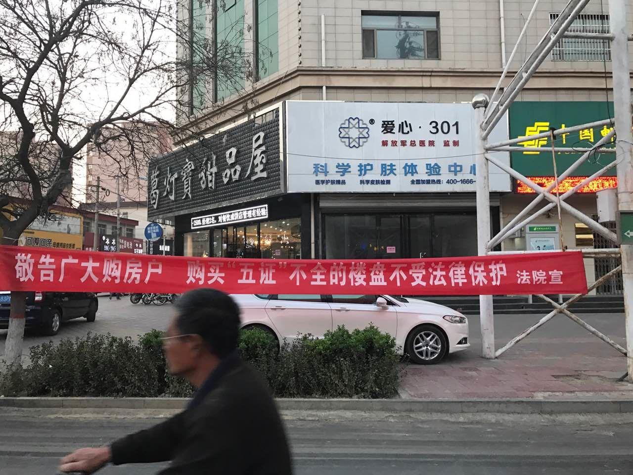 """安新法院在该县街头挂出""""敬告购房者""""横幅。"""