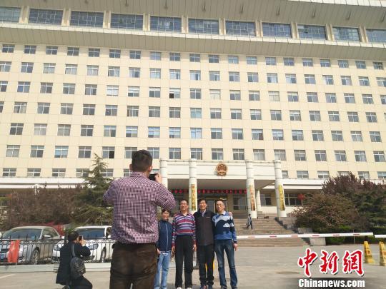 外地游客在雄县政府大楼前拍照留念 王天译 摄