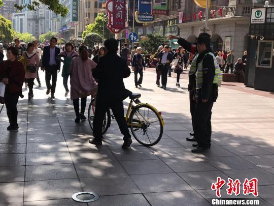 两名共享单车骑行者在执勤职员的劝止下下车履行。 王子涛 摄
