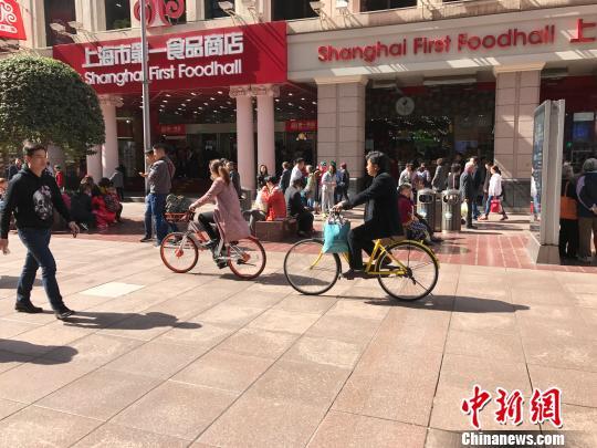 两名骑行者将共享单车骑上了上海南京路步行街。 王子涛 摄