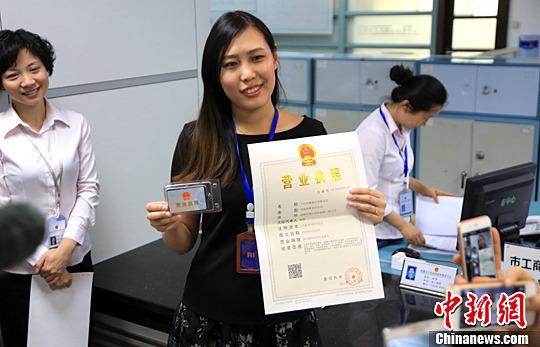 资料图:公司人员展示其领取的营业执照。中新社发 钟欣 摄
