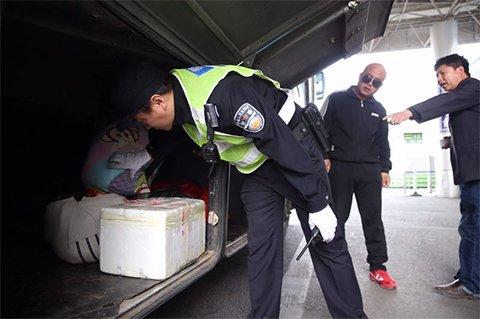 民警对进京大巴车的行李箱进行检查。新京报记者 尹亚飞 摄