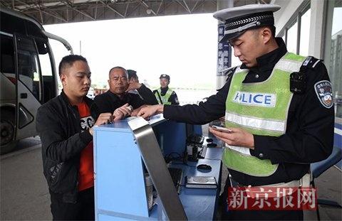 民警对进京大巴车上乘客们的身份证进行检查核实。新京报记者 尹亚飞 摄