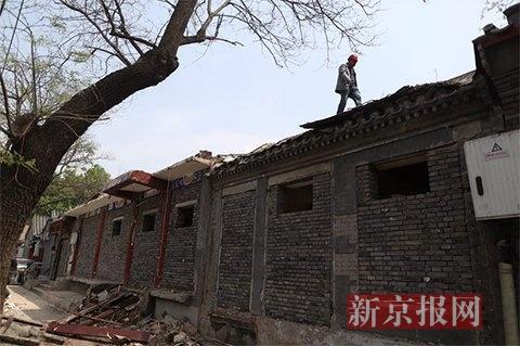 2017年4月13日,景山东街一处临街建造边,数名工人撤除并添堵违规建造。新京报记者 侯少卿 摄