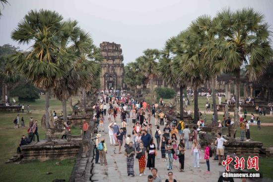 资料图:上千名各国游客早早守候在柬埔寨暹粒景点——吴哥窟,守候观看日出。中新社记者 洪坚鹏 摄