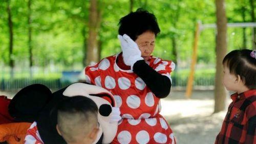 72岁的银丕芝老人身穿米老鼠演出服,与游客合影收取费用,为病床上的儿媳妇募集治疗费。