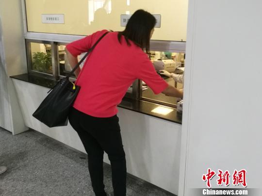 图为患者在窗口送检验液体。 张枭 摄