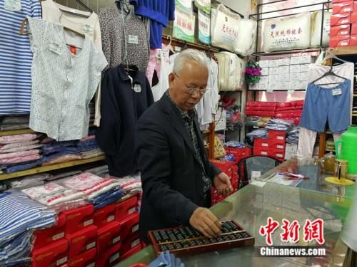 61岁的售货员张志国至今仍在使用算盘 中新网记者 张尼 摄