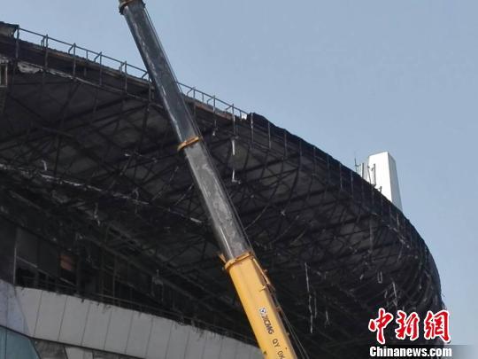 27日早上,记者在被扑灭的大火现场看到,体育中心北大门中间以上大型外观面弧形部位至外观点最高处内部钢架已裸露在外。 王祎 摄
