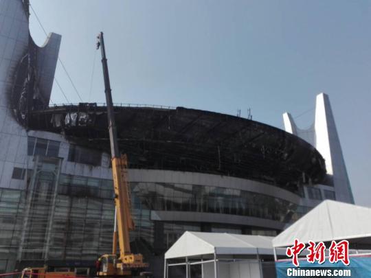图为27日早上,记者在被扑灭的大火现场看到,体育中心北大门中间以上大型外观面弧形部位至外观点最高处内部钢架已裸露在外。 王祎 摄