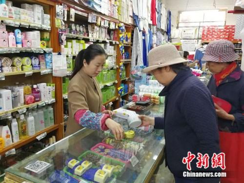 顾客在永安路百货商场化妆品柜台挑选商品 中新网记者 张尼 摄