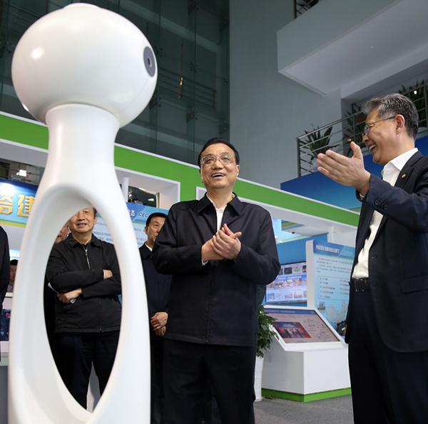 """李克强4月27日考察央企""""双创""""成效展时,在智能单车锁、迷你洗衣机、磁悬浮桌面音箱、人体动作捕捉传感器等创新产品前不时驻足。一位世界500强的央企""""巨头""""不好意思地对总理说,我们这里都是""""小产品""""。总理说,小产品有大市场。中国政府网 图"""