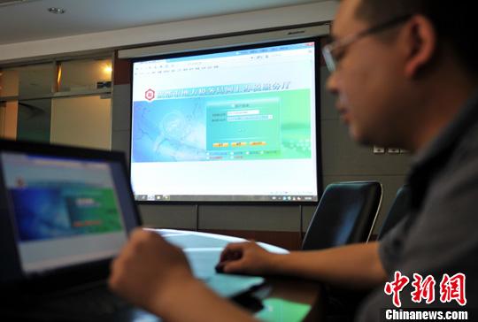 图为事情职员正在先容网上购发票流程。中新社发 刘忠俊 摄