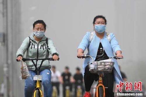 资料图:民众在沙尘天气中出行。 中新社记者 武俊杰 摄