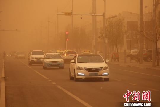 内蒙古地区迎来今年最强沙尘暴,图为车辆在沙尘中缓慢行驶。 李爱平 摄
